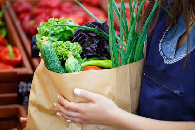 Sluit omhoog van een document zak met aankopen in de handen van een vrouw bij een groentewinkel