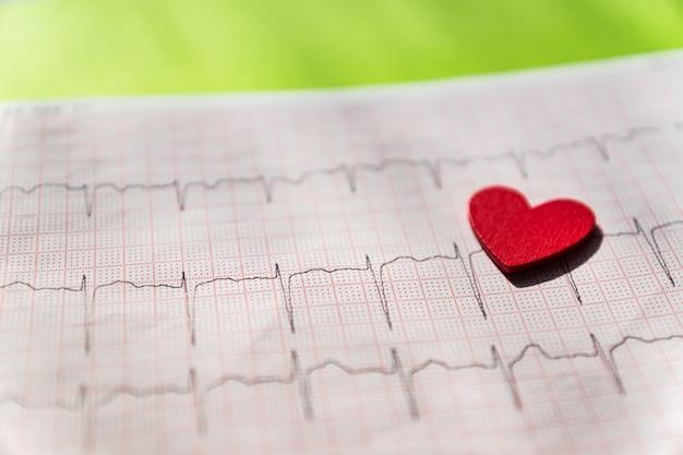 Sluit omhoog van een elektrocardiogram in document vorm vith rood houten hart. ecg- of ecg-papier op zwart. medisch en gezondheidszorgconcept.