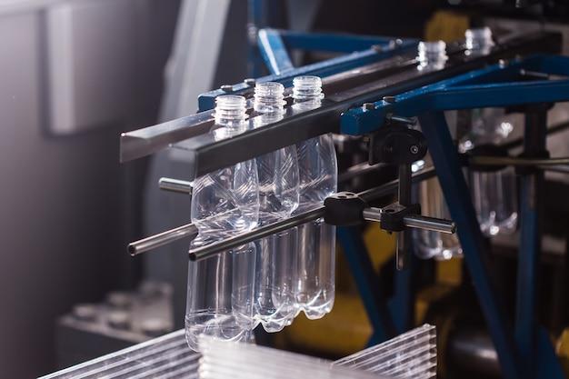 Sluit omhoog van een flessenindustrie. close-up op mineraalwaterflessen in ruw en lijnen