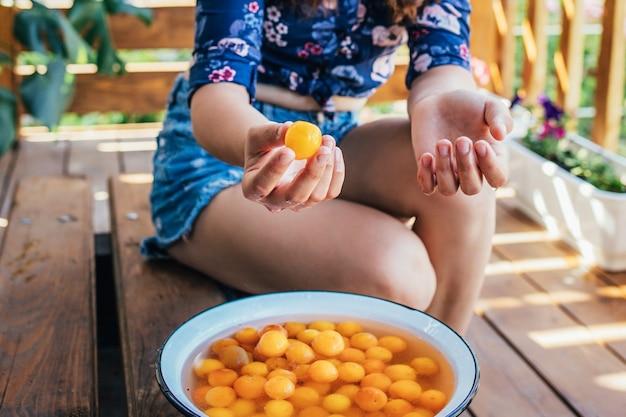 Sluit omhoog van een fruit van de meisjeswas in een kom met water