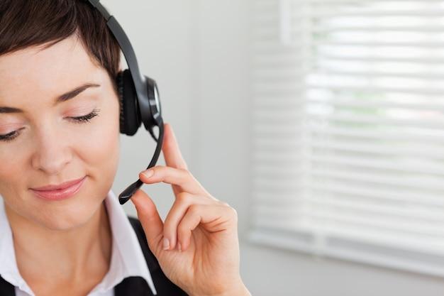 Sluit omhoog van een geconcentreerde secretaresse die met een hoofdtelefoon roept