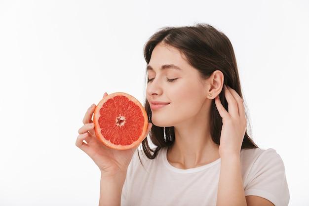 Sluit omhoog van een gelukkige jonge mooie geïsoleerde vrouw, die vers gesneden grapefruit toont