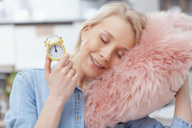 Sluit omhoog van een gelukkige mooie vrouw die kleine wekker houdt, liggend op pluizig roze hoofdkussen