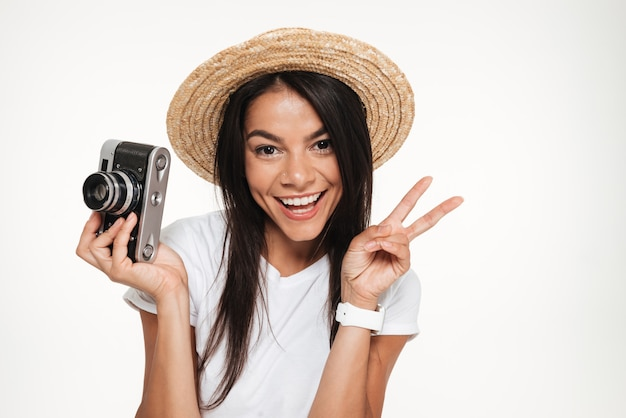 Sluit omhoog van een glimlachende jonge vrouw in hoed