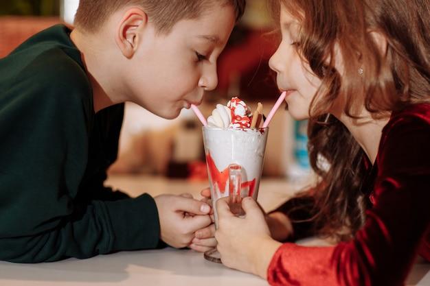 Sluit omhoog van een glimlachende jongen en meisje die met twee rietjes drinken