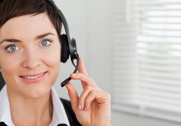 Sluit omhoog van een glimlachende secretaresse die met een hoofdtelefoon roept