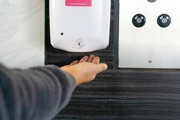 Sluit omhoog van een hand die de dispenser van het ontsmettingsgelgel gebruikt