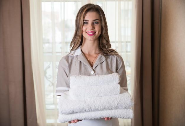 Sluit omhoog van een jong hotelmeisje houdend schone gevouwen handdoeken