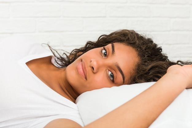 Sluit omhoog van een jonge afrikaanse amerikaanse vermoeide vrouw liggend op het bed