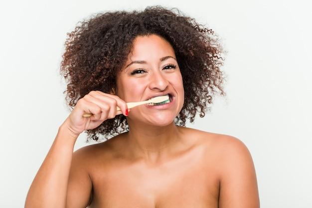 Sluit omhoog van een jonge afrikaanse amerikaanse vrouw die haar tanden met een tandenborstel borstelt