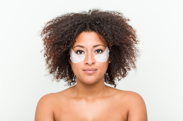 Sluit omhoog van een jonge afrikaanse amerikaanse vrouw met een behandeling van de ooghuid