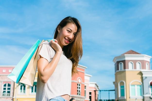 Sluit omhoog van een jonge aziatische vrouw die een openluchtvlooienmarkt met een achtergrond van pastel buliding winkelt