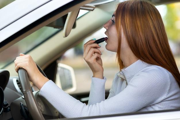 Sluit omhoog van een jonge bestuurder die van de roodharigevrouw haar make-up verbetert