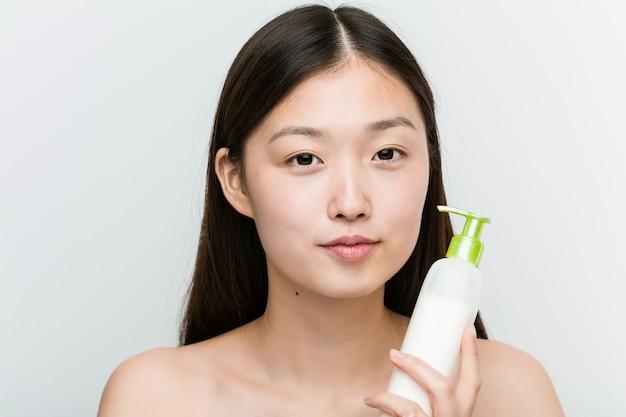 Sluit omhoog van een jonge mooie en natuurlijke aziatische vrouw die een bevochtigende roomfles houden