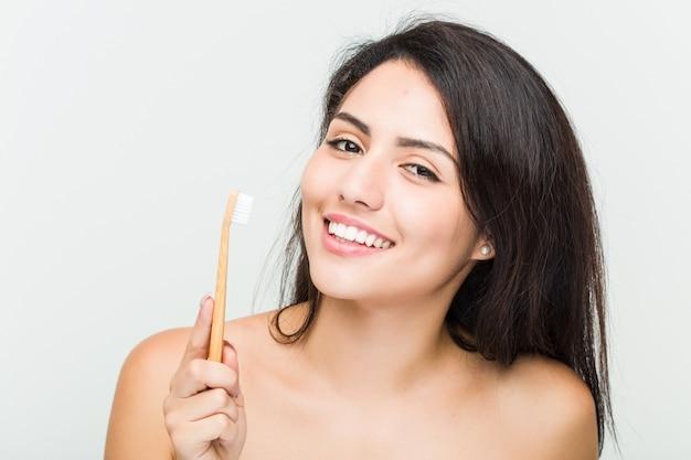 Sluit omhoog van een jonge mooie en natuurlijke spaanse vrouw die een tandenborstel houden