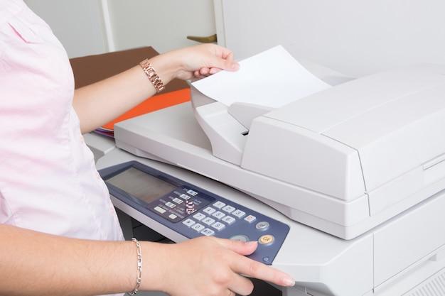 Sluit omhoog van een jonge secretaresse gebruikend een exemplaarmachine