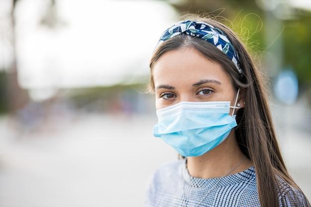 Sluit omhoog van een jonge vrouw die een beschermend masker draagt