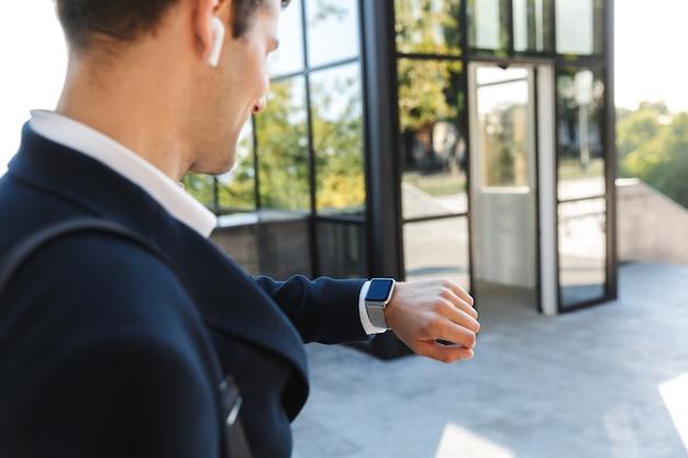 Sluit omhoog van een jonge zakenman die kostuum draagt dat polshorloge in openlucht bekijkt