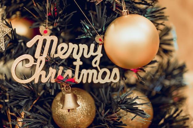 Sluit omhoog van een kerstboom en een decoratie met gouden bal en engelse tekst vrolijke kerstmis.