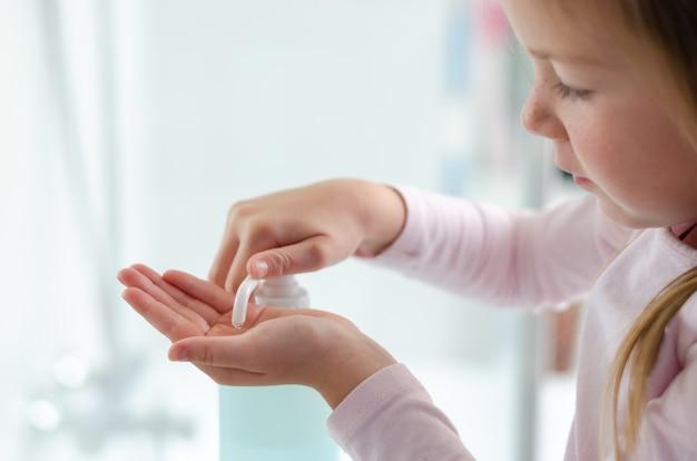 Sluit omhoog van een klein meisje gebruikend desinfecterend middel van het handdesinfecterend middel