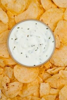 Sluit omhoog van een kom witte onderdompeling die door nachos wordt omringd
