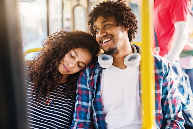 Sluit omhoog van een leuk vermoeid krullend meisje dat haar hoofd op de schouder van haar vriendje leunt terwijl het zitten in een bus.