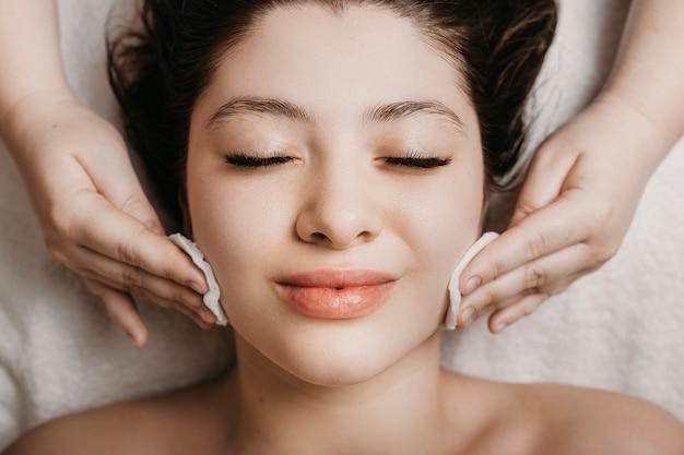 Sluit omhoog van een leuke jonge vrouw die gezichts routine huidzorg in een wellness-kuuroord doet.