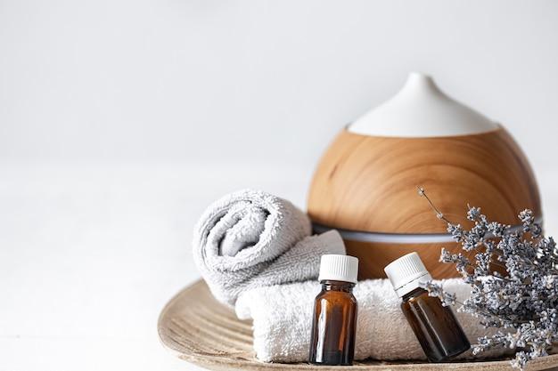 Sluit omhoog van een luchtbevochtiger, natuurlijke aromatische oliën, handdoeken en lavendeltwijgen. aromatherapie en gezondheidszorg concept achtergrond
