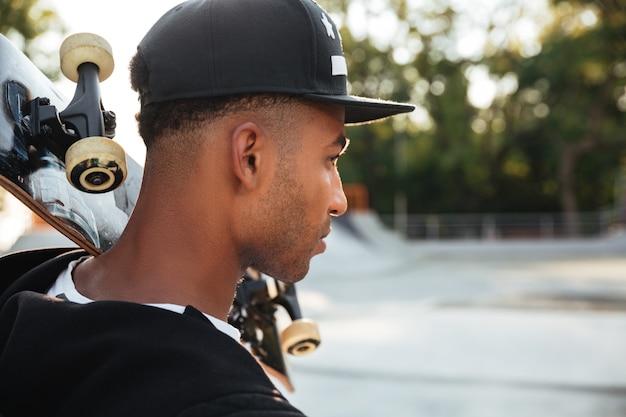 Sluit omhoog van een mannelijk de holdingsskateboard van de tienerkerel