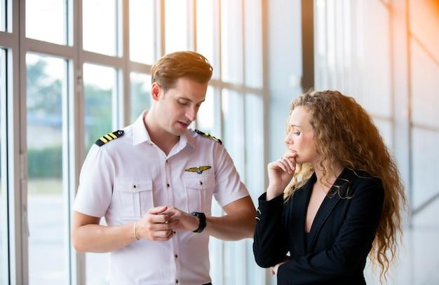 Sluit omhoog van een mannelijk glas van de helikopter proefslijtage en bedrijfsmensen of uitvoerende ceo die zich tegen helikopter op vliegtuigenlandingspunt bevinden in luchthaven op een heldere zonnige dag.