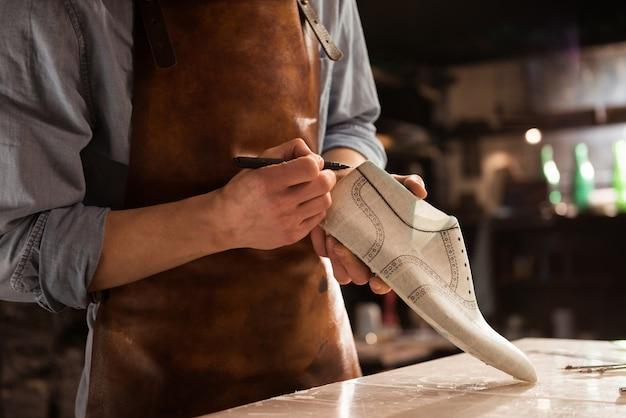 Sluit omhoog van een mannelijk ontwerp van de schoenmakerstekening