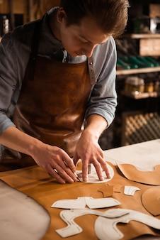 Sluit omhoog van een mannelijke schoenmaker die met leertextiel werkt