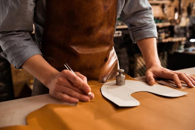 Sluit omhoog van een mannelijke textiel van het schoenmakers scherpe leer
