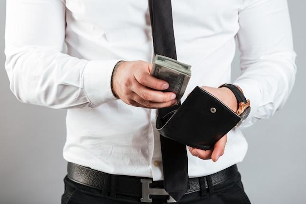 Sluit omhoog van een mens die contant geld in zijn portefeuille zet