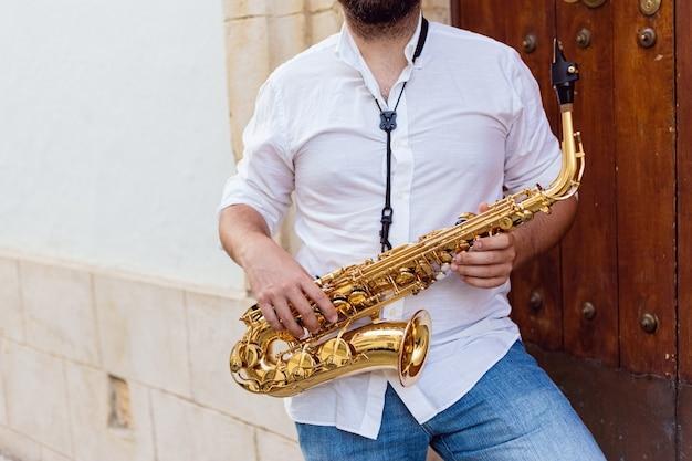 Sluit omhoog van een mens die hartstochtelijk zijn saxofoon speelt bij de deur van een gebouw op straat