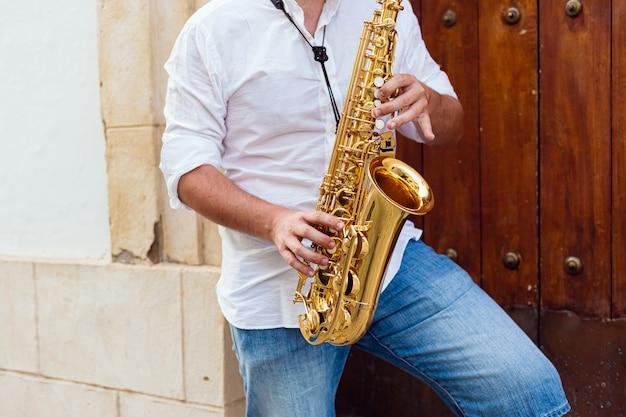 Sluit omhoog van een mens die zich bij een deur van een gebouw op de straat bevindt die de saxofoon speelt
