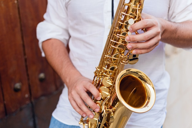 Sluit omhoog van een mens die zijn saxofoon op de straat houdt