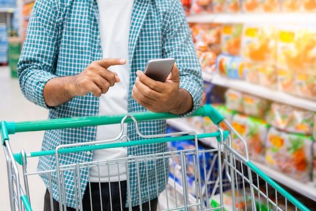 Sluit omhoog van een mens gebruikend smartphone en winkelend in een supermarkt, het winkelen concept