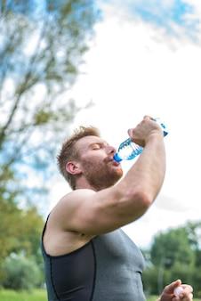 Sluit omhoog van een mensen drinkwater van een fles buiten