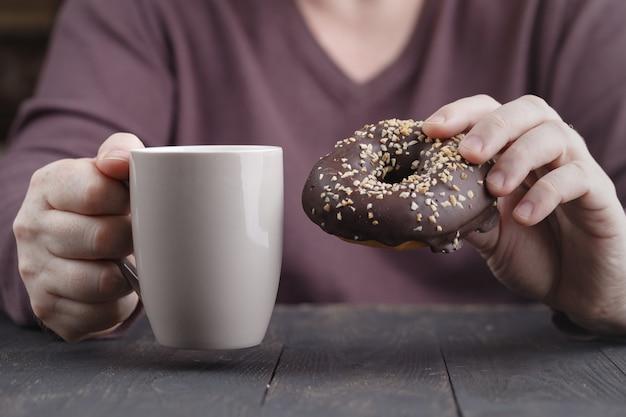 Sluit omhoog van een mensenholding in zijn handen een doughnut met chocolade