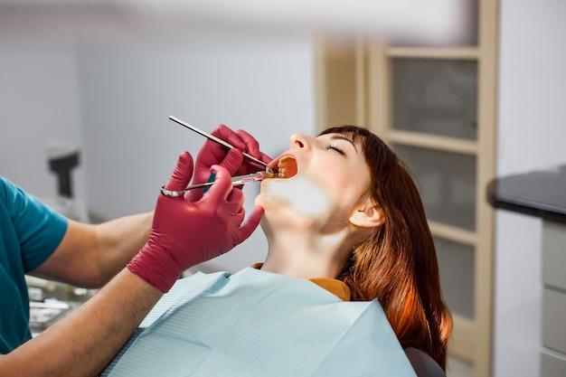 Sluit omhoog van een mensentandarts in rode medische handschoenen die zijn jonge patiënt een anesthesieinjectie in tandkliniek geven