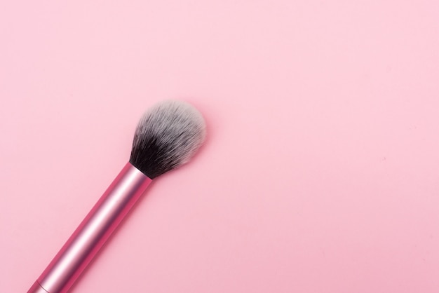 Sluit omhoog van een merk op borstel. make-up kwast voor poeder foundation geïsoleerd op roze achtergrond