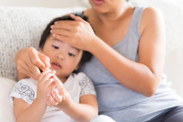 Sluit omhoog van een moeder die de temperatuur van haar zieke baby controleert