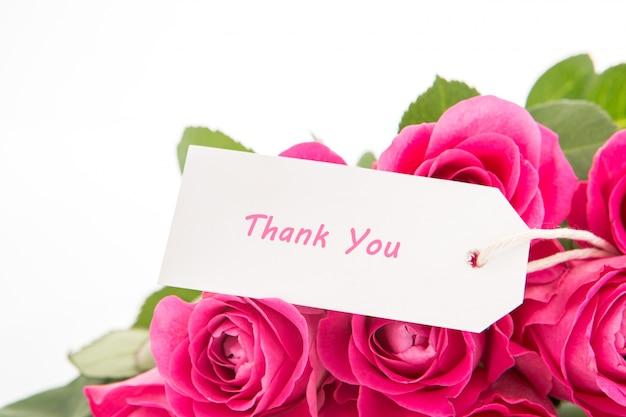 Sluit omhoog van een mooi boeket van roze rozen met dank u kaarden op een witte achtergrond