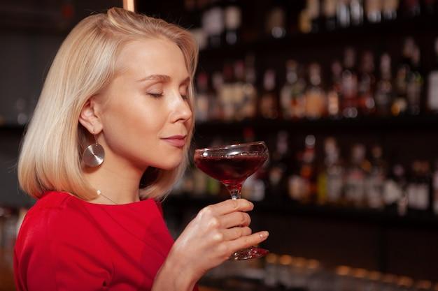 Sluit omhoog van een mooie blonde vrouw glimlachend met haar gesloten ogen het hebben van een drankje aan de bar in de avond