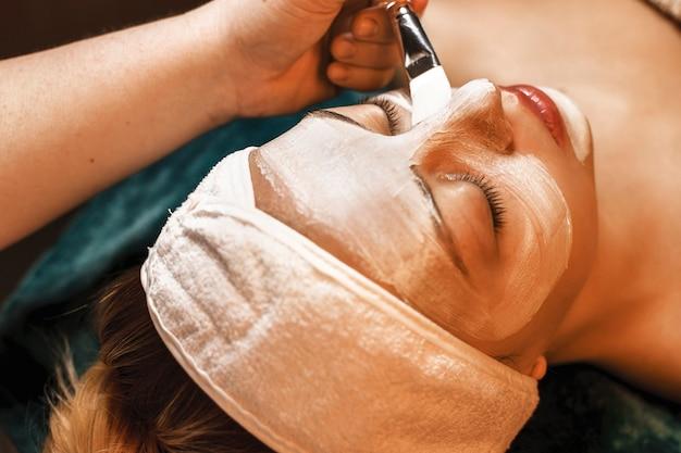 Sluit omhoog van een mooie jonge vrouw die in een kuuroordsalon leunt met gesloten ogen doet een anti-acne wit masker.