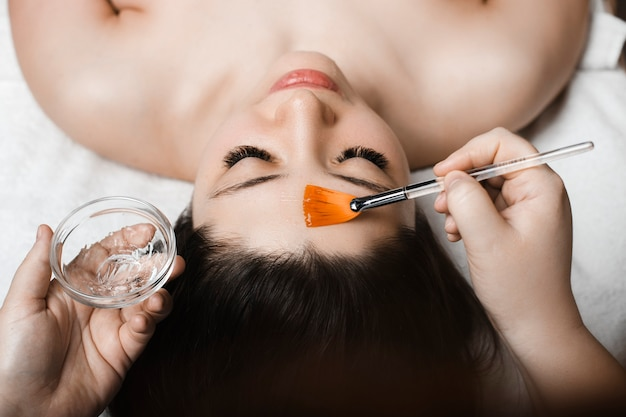 Sluit omhoog van een mooie jonge vrouw die met gesloten ogen op een kuuroordbed leunt met een gezichtshydratatiemasker