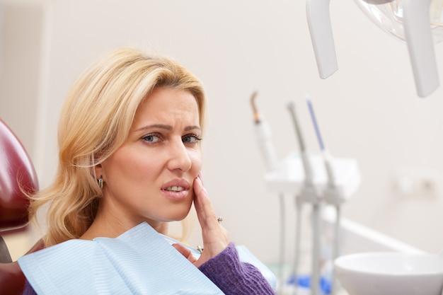 Sluit omhoog van een mooie rijpe vrouw die uitgeput lijdend aan tandpijn kijkt