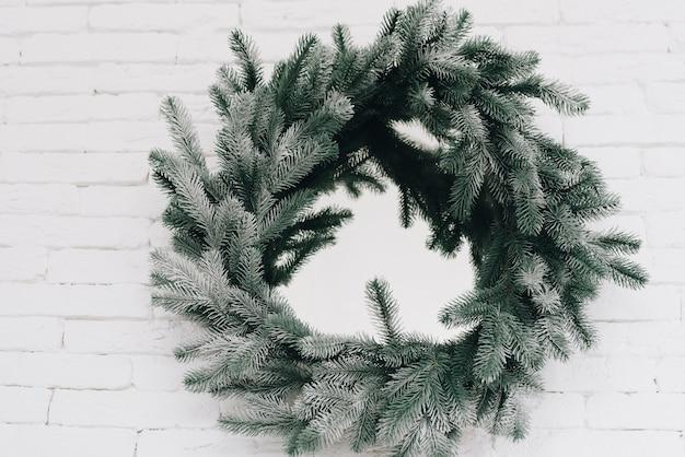 Sluit omhoog van een mooie subtiele kroon van kerstmis op een wit