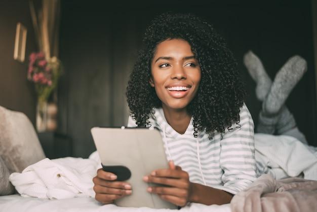 Sluit omhoog van een mooie zwarte die met krullend haar en telefoon op bed glimlacht gebruikt weg kijkend